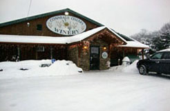 Conneaut Cellar Winery building in Conneaut Lake PA is shown covered in snow as customers enter the gift shop during the holidays.