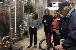 Conneaut Cellars Winery Visitors shown touring through the wine aging room.